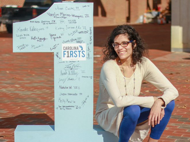 "Srividya Kalyanaraman sits by a large ""1"" representing first-generation students."