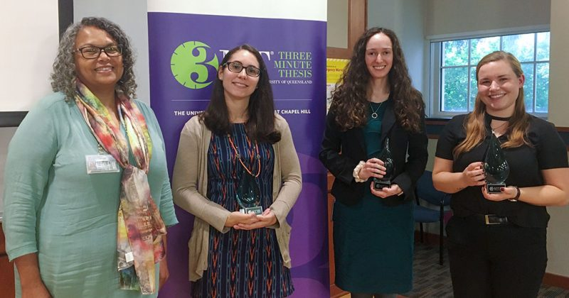 Four women stand in front of the Three Minute Thesis banner.