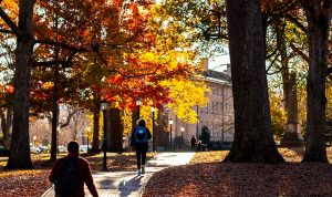 Students walking on campus walkways surrounded by fall colors.