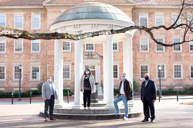 Four people and stand spaced apart in front of UNC's Old Well wearing face masks.