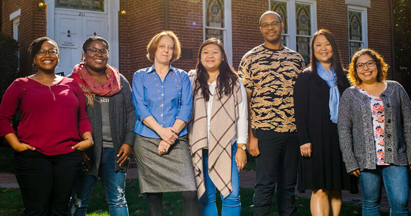 Members of the diversity and student success program pose on the lawn in front of a university building