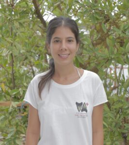 Isabel Silva Romero standing in front of a tree and wearing a white t-shirt.