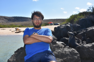Diego Urquía sitting outdoors at his research site outdoors near water.
