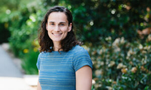 Headshot of Marisa Marraccini, who is wearing a blue shirt and standing in front of greenery.