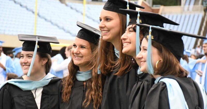 Graduate student alumni smiling and wearing regalia.